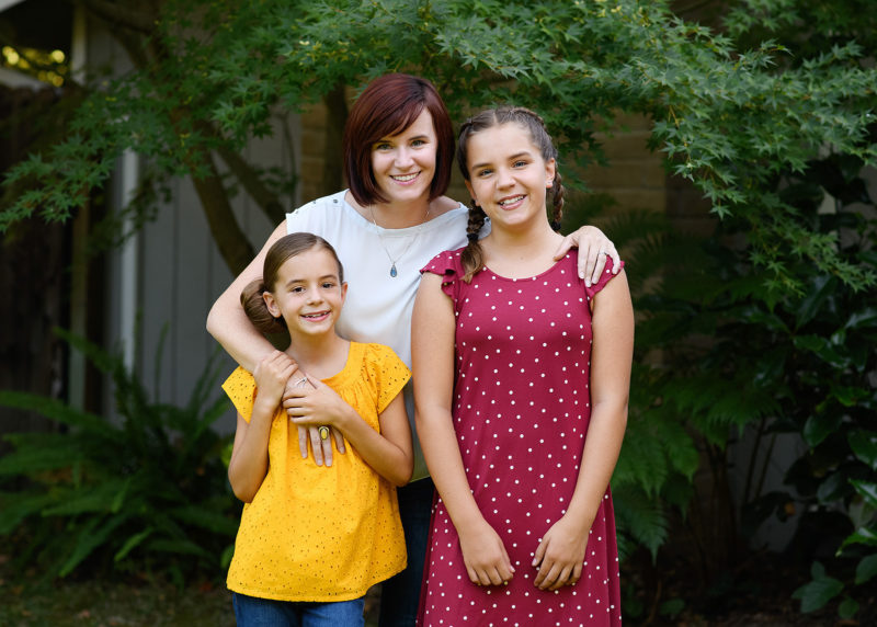 Mom and daughters smiling directly at camera with trees and Fair Oaks home as background