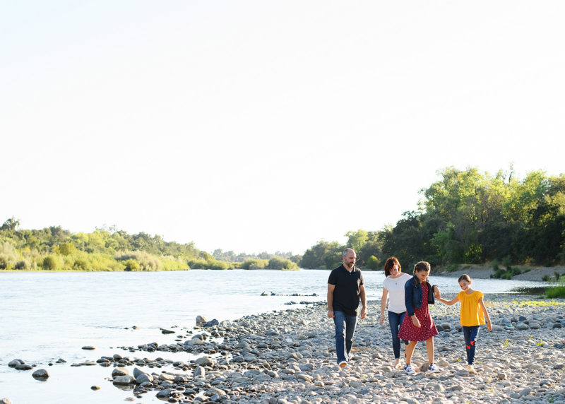 Family walking along river on smooth rocks in Fair Oaks