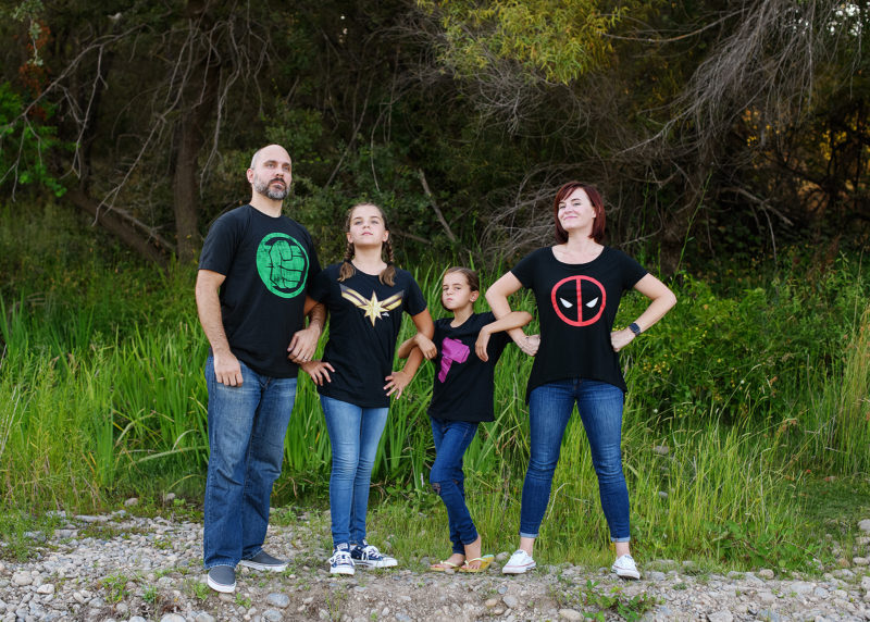 Family wearing superhero shirts striking a pose outside in Fair Oaks