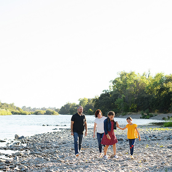 Family walking along river on smooth rocks