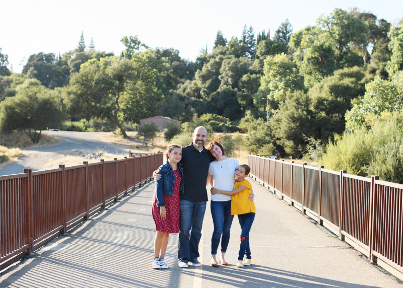 family hugs on a bridge in fair oaks sacramento