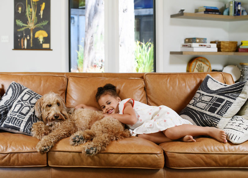 Daughter and dog lying down on brown leather couch in Mendocino home