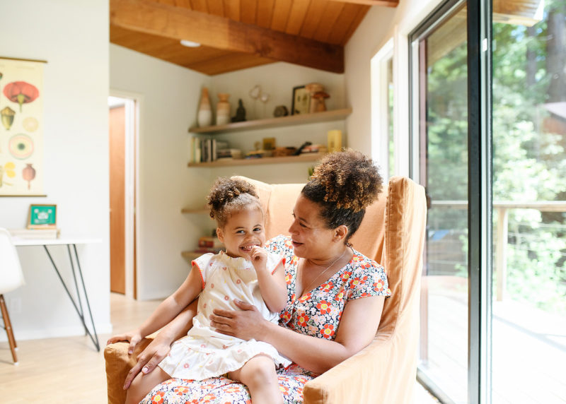 Mom and daughter sitting on armchair surrounded by natural light in Mendocino home