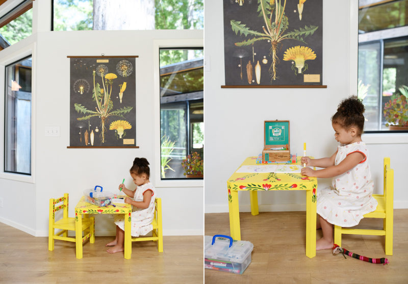 Toddler girl coloring on yellow kids table under botanical print in Mendocino home