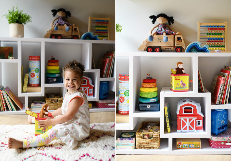 Toddler girl in playroom with details of toys on bookshelf in Mendocino home