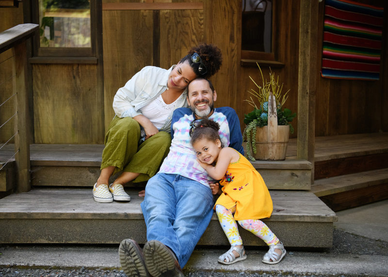 Mom, dad and daughter on backyard steps cuddling with each other in Mendocino home