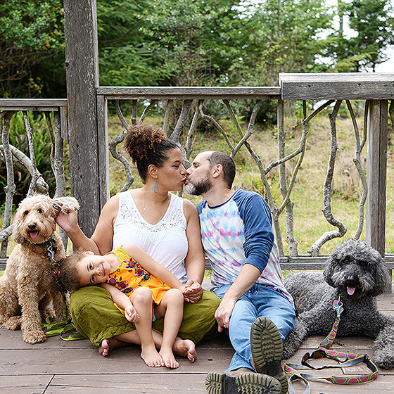 Mom and dad kiss while daughter and dogs look directly at camera while sitting on outdoor deck in Mendocino park
