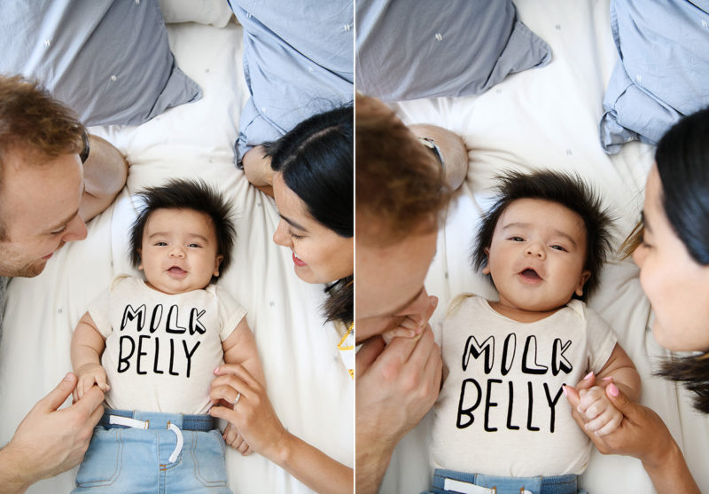Baby boy lying in bed with mom and dad wearing a Milk Belly onesie in Sacramento home