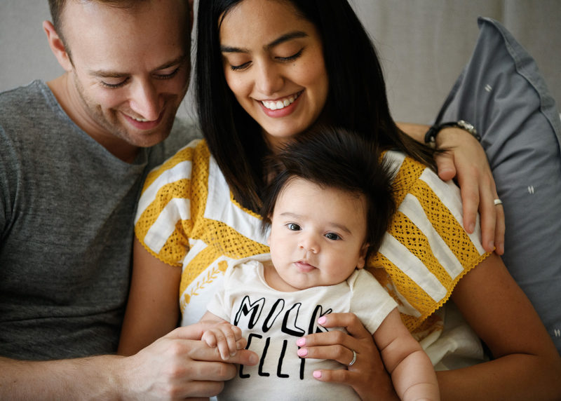Mom and dad snuggle their baby boy in bed in Sacramento home