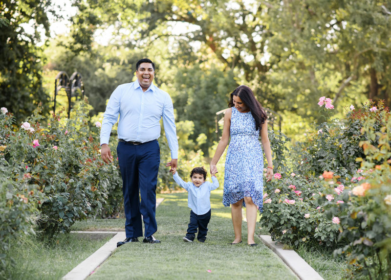 Mom and dad holding on to one year old boy's hands as they walk through McKinley Park Rose Garden Sacramento