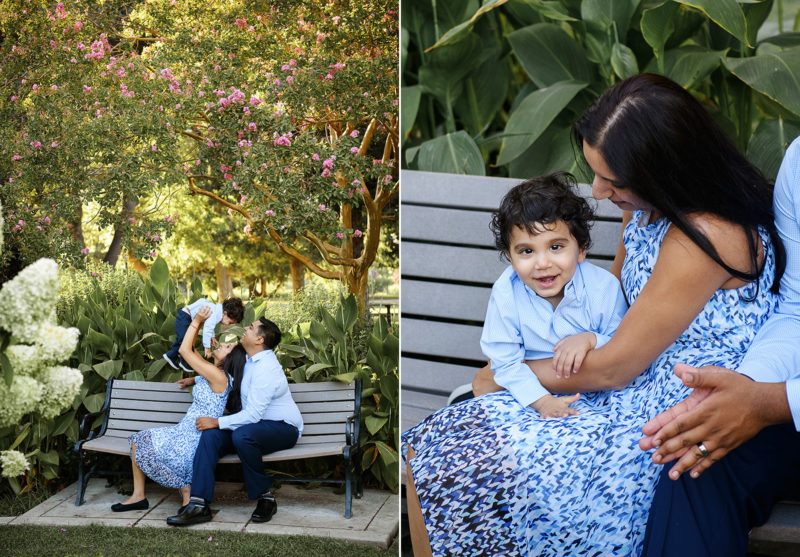 Mom and dad sitting on bench with baby boy in McKinley Park Sacramento surrounded by flowers