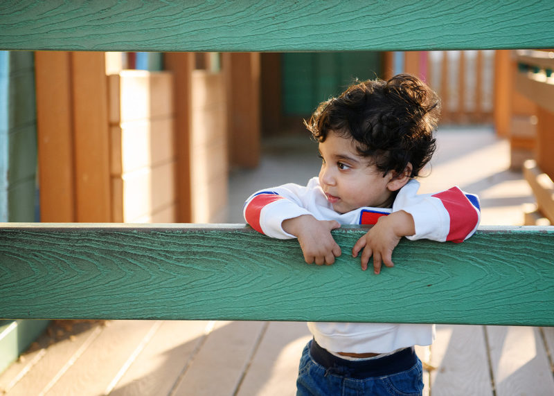 One year old boy leaning against green fence in McKinley Park playground
