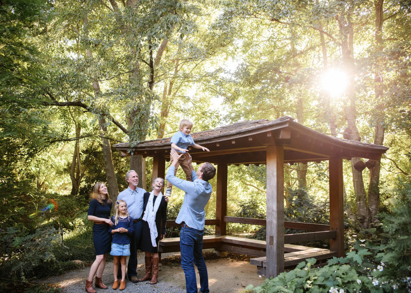 Dad lifting up son in air while grandparents, mom and sister watch next to pergola in Quarryhill Botanical Garden Sonoma