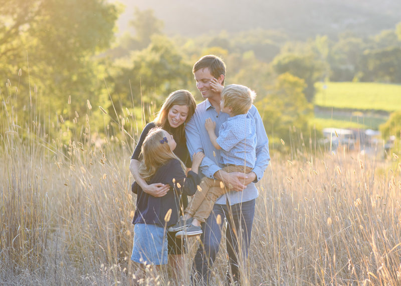Family hugging in tall yellow grass during sunset in Quarryhill Botanical Garden Sonoma