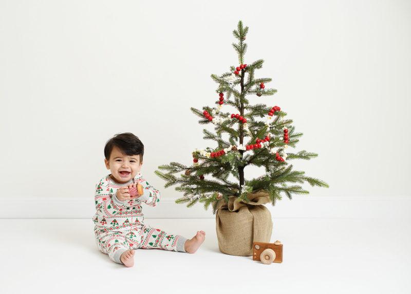 Baby boy wearing pajamas next to Christmas tree and toy camera in Sacramento studio