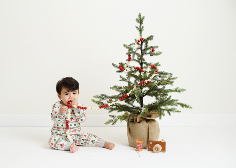 Baby boy mouthing Christmas garland from the tree while wearing pajamas in Sacramento studio