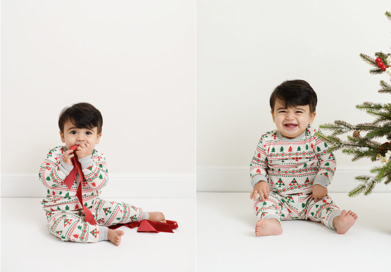 Baby boy sitting on studio floor eating ribbon and smiling next to Christmas tree
