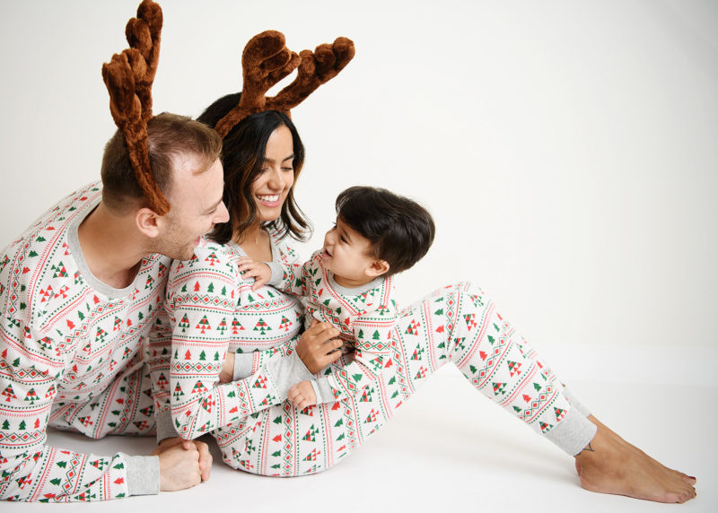 Family wearing Christmas pajamas and reindeer antlers while holding baby boy