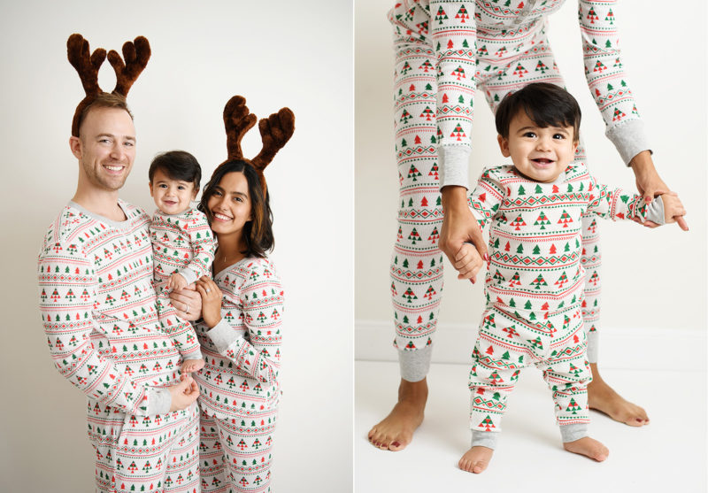 Mom and dad hold baby boy wearing matching Christmas pajamas and reindeer antlers in studio