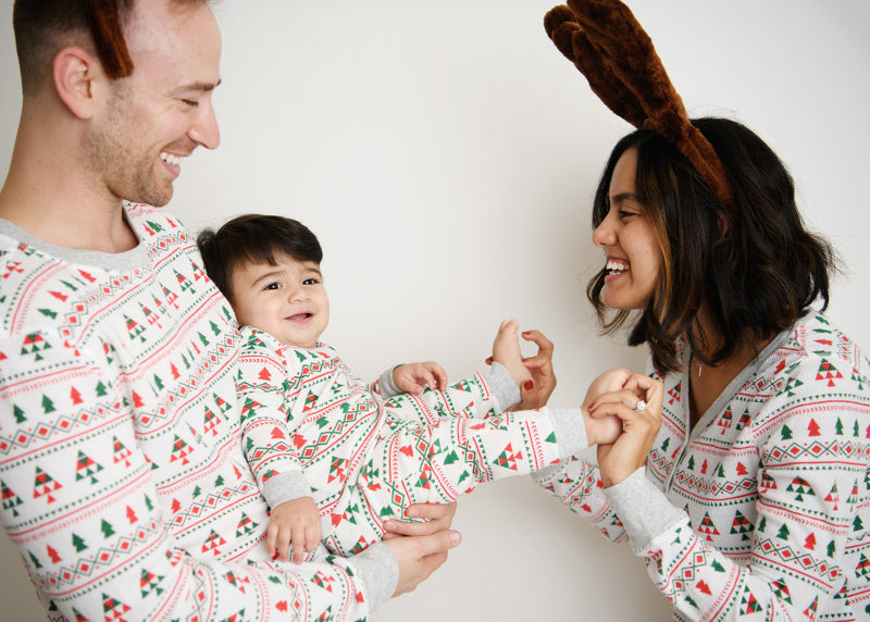 Mom holds baby boy's feet as dad holds him wearing matching Christmas pajamas in studio