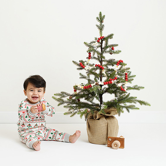 Baby boy wearing pajamas next to Christmas tree and toy camera
