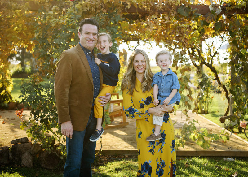 Mom and dad holding sons and smiling with sprawling tree in background in Sacramento Valley farm