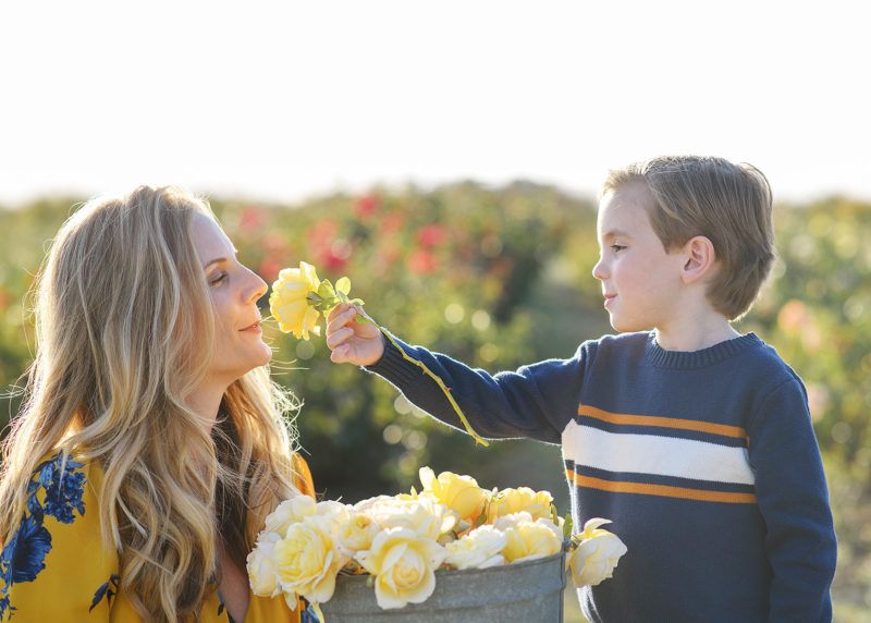 Son handing rose to mom so she can smell it in Sacramento Valley flower farm