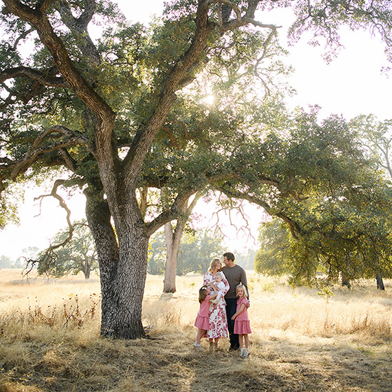 Family under a sprawling tree in dry grass in Folsom