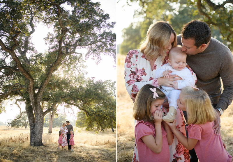 Family standing under large tree and kissing baby brother in Folsom