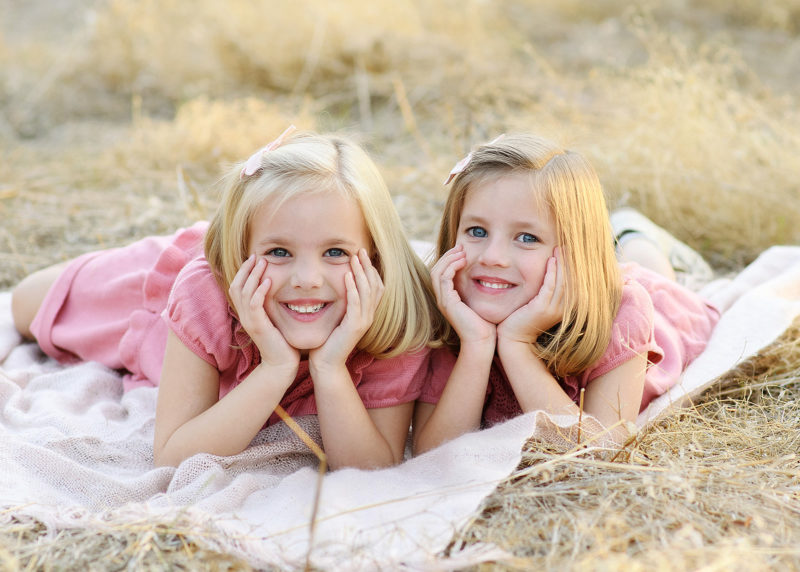 Twin sisters lying down on white blanket and smiling in Folsom