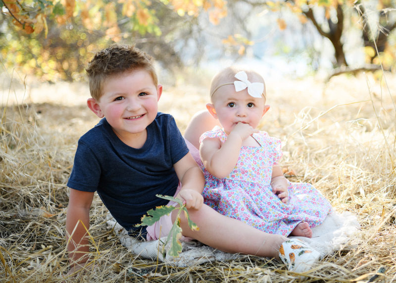 Big brother and baby sister sit on dry grass smiling in Folsom