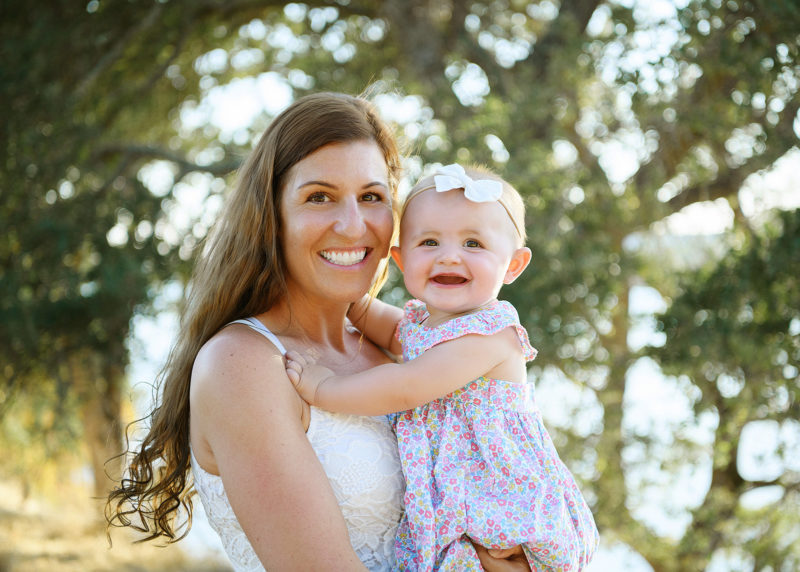 Mom holding baby daughter and smiling with trees in the background in Folsom