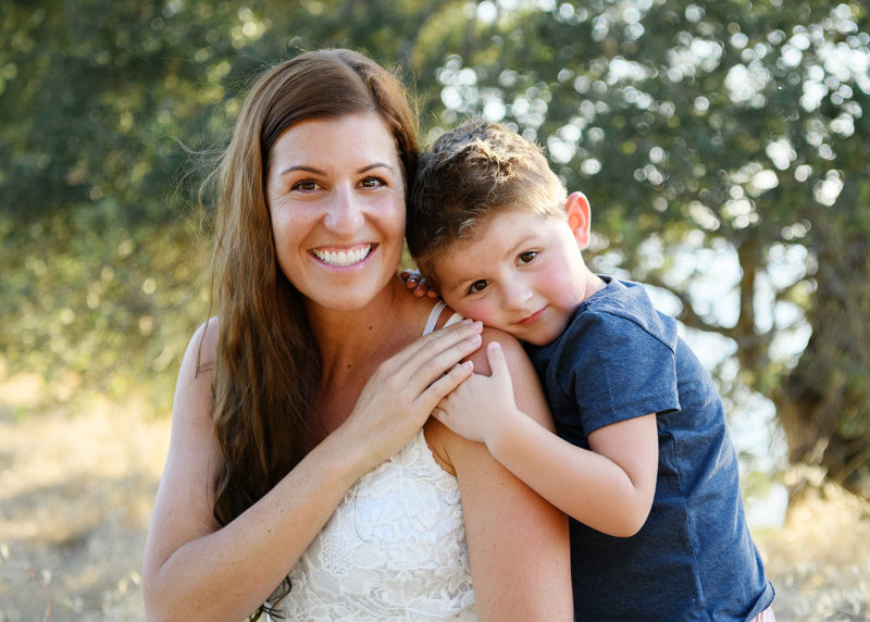 Mom smiles at the camera with son hugging her with trees in background in Folsom
