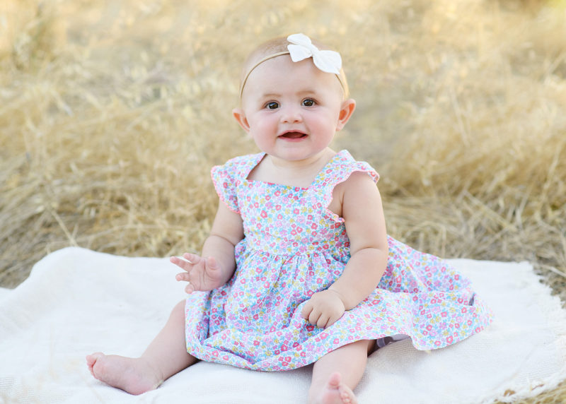 Baby girl wearing a bow and floral print dress sitting on blanket outdoors in Folsom