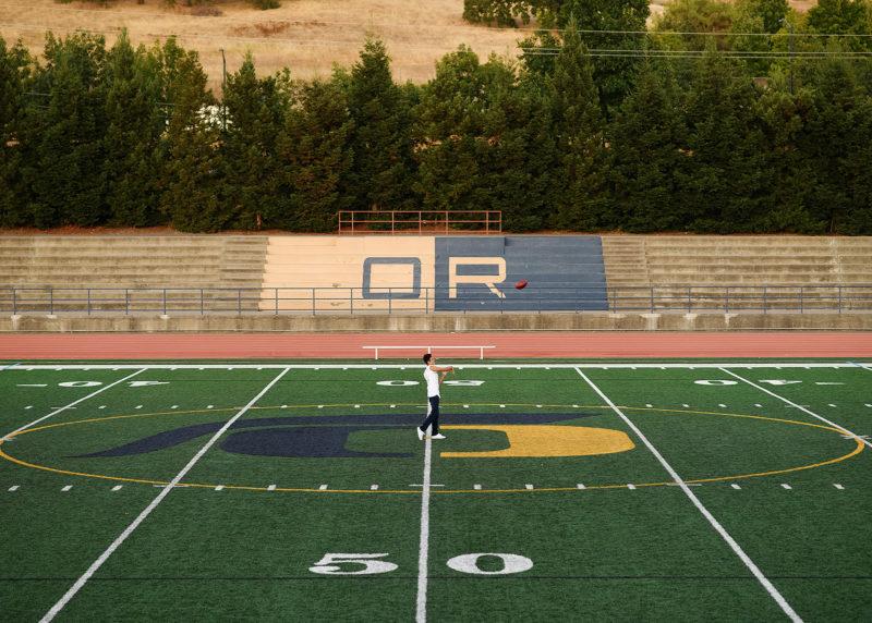 Wide shot of senior football player in Oak Ridge High School football field