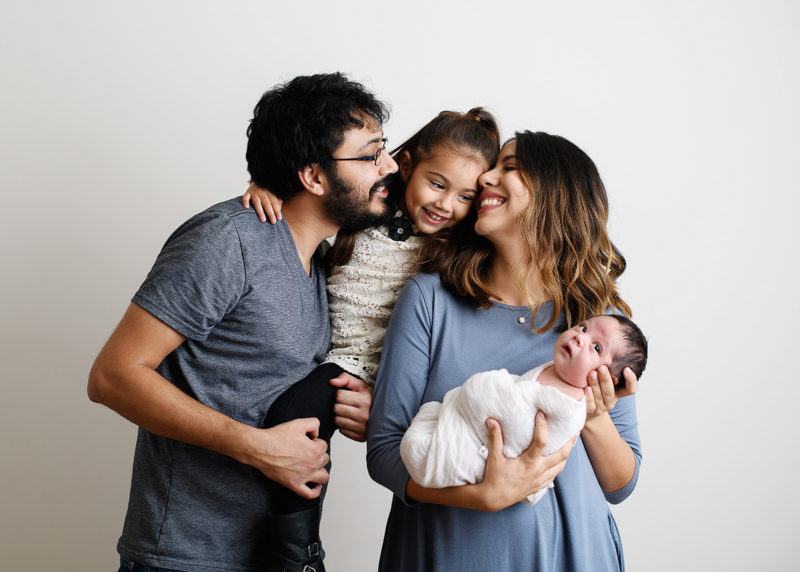 Family photo holding a newborn baby with big sister looking lovingly at baby in studio