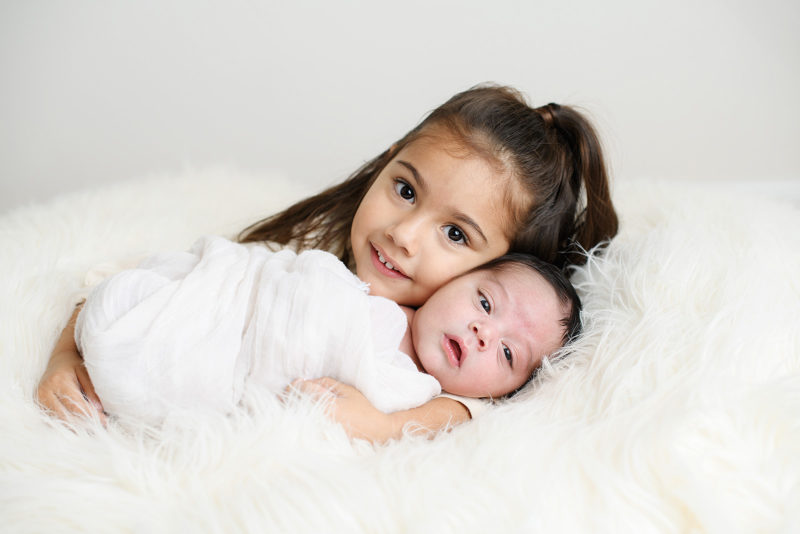 Big sister snuggling with newborn baby on sheepskin rug in studio