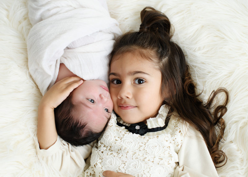 Big sister looking directly at camera while holding newborn baby close to cheek in studio