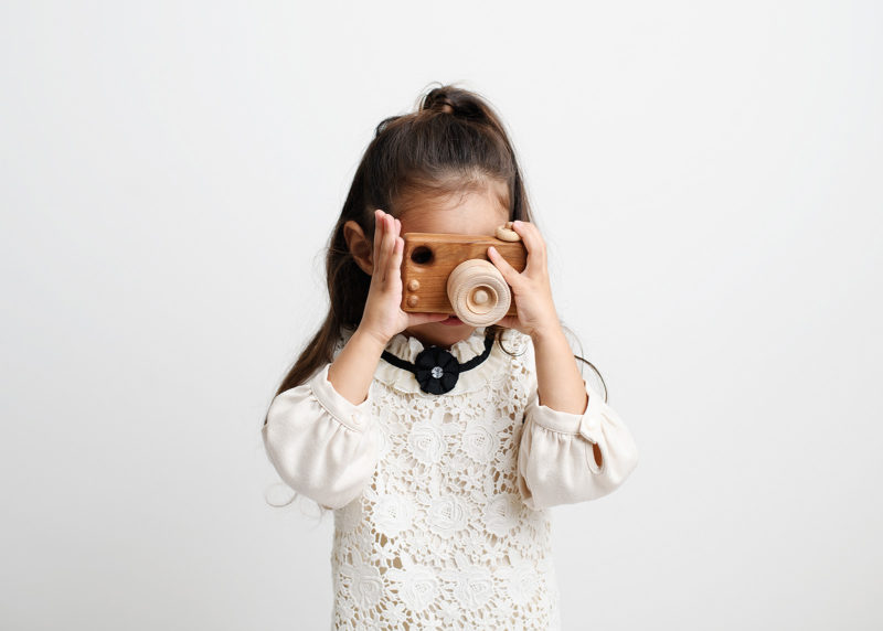 Big sister holding a wooden toy camera against white studio wall