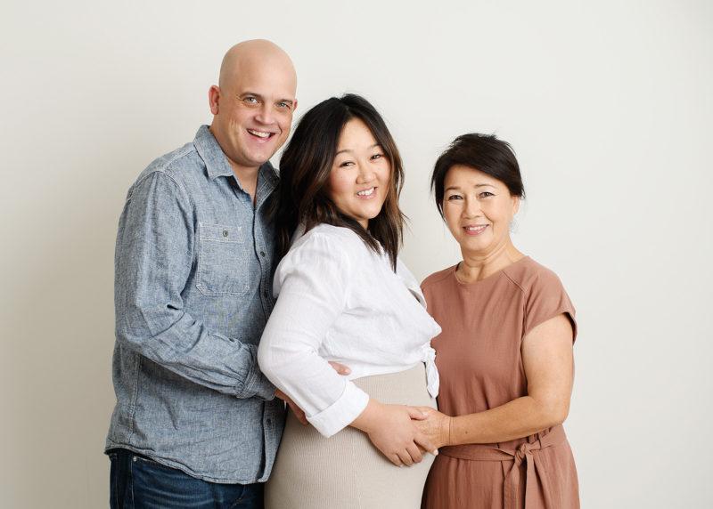 Husband, pregnant wife and mom hugging in Sacramento studio