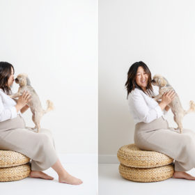 Maternity photo with Asian pregnant woman kissing her dog while sitting on rattan cushions in Sacramento studio