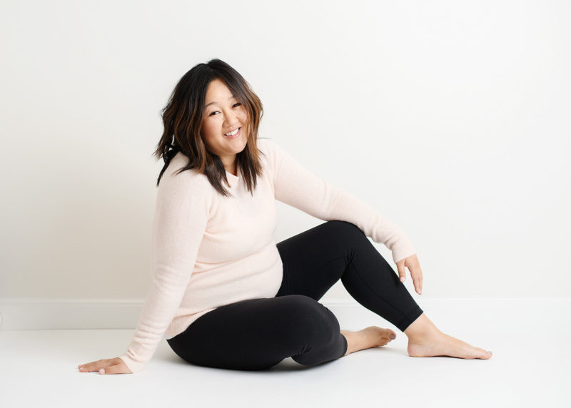 Pregnant Asian woman smiling and casually sitting on Sacramento studio floor