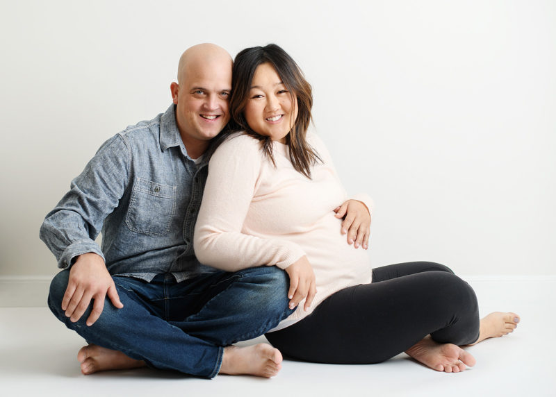 Pregnant mom and dad sitting on the floor and hugging in Sacramento studio