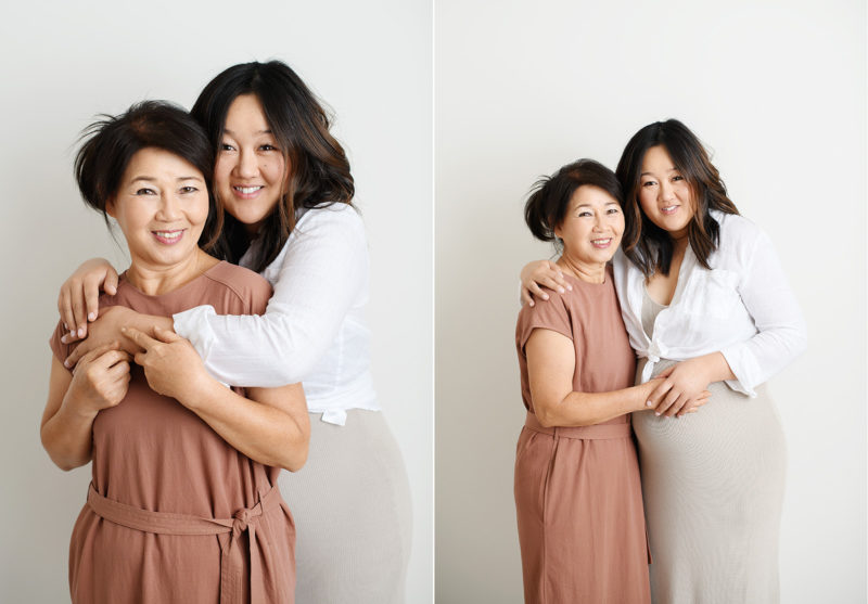 Asian mother and pregnant daughter embracing in Sacramento studio