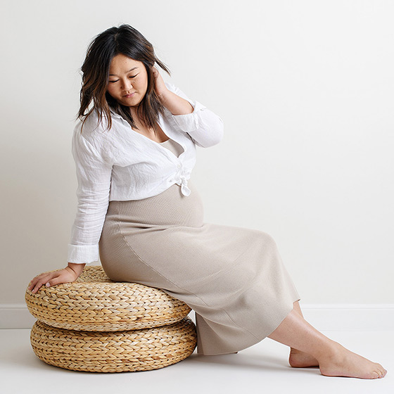 Maternity photo with pregnant Asian women sitting on rattan cushions in Sacramento studio