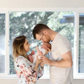 Dad kissing sleeping newborn bay as mom holds him in floral robe in Sacramento home