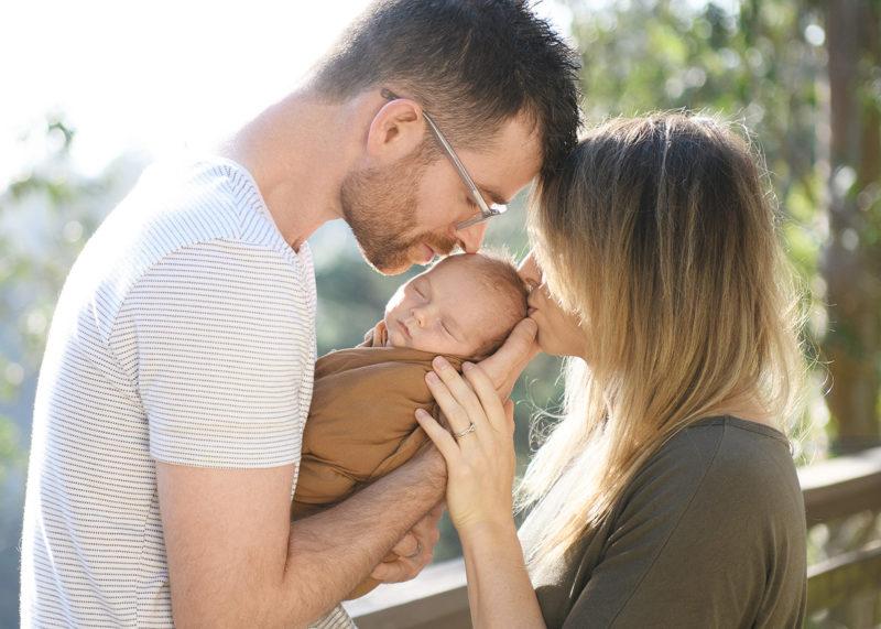 Mom and dad lovingly kiss sleeping newborn baby outside
