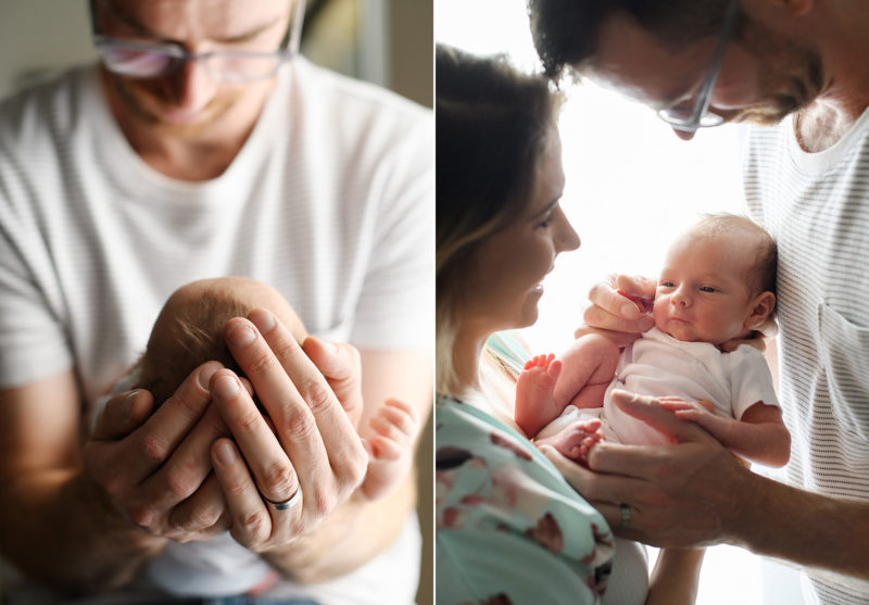 Dad holding newborn baby's head and mom and dad holding newborn baby against natural light window in Oakland home