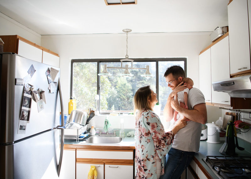 Dad holding newborn baby as mom looks on in kitchen lifestyle photo