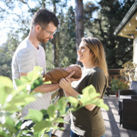 Mom and dad holding newborn baby outside on deck surrounded by trees